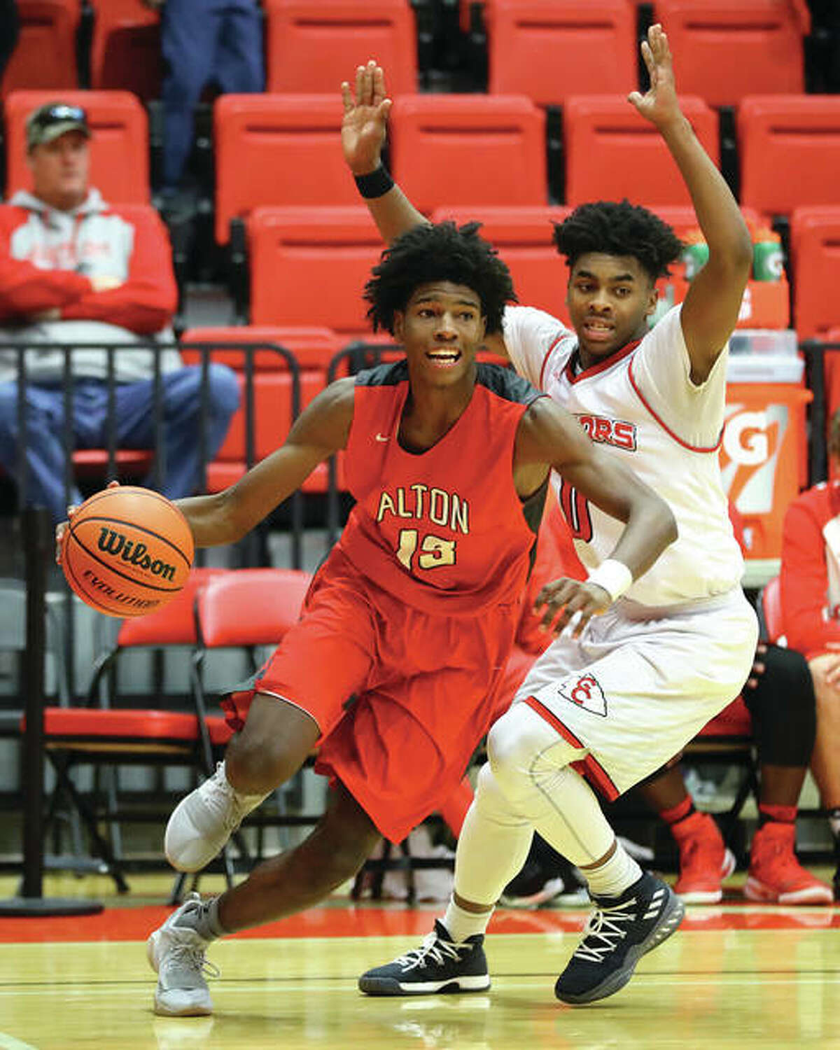 Alton's Malik Smith (left) drives the baseline after getting past Granite City's Jerry Watson during Saturday's game at SIUE's Vadalabene Center.