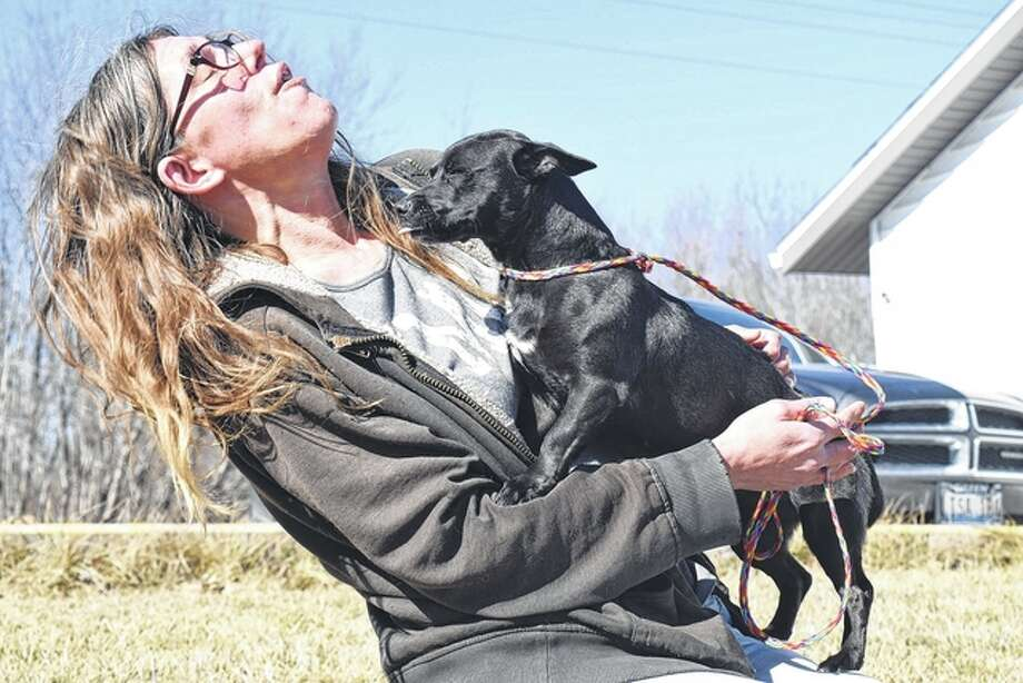 Kris Stocker, an employee at the Morgan County Animal Shelter, gives Chica, a young Chihuahua mix, a few pets during an afternoon stroll Friday. Chica will be up for adoption Feb. 21, assuming she is not claimed before then.