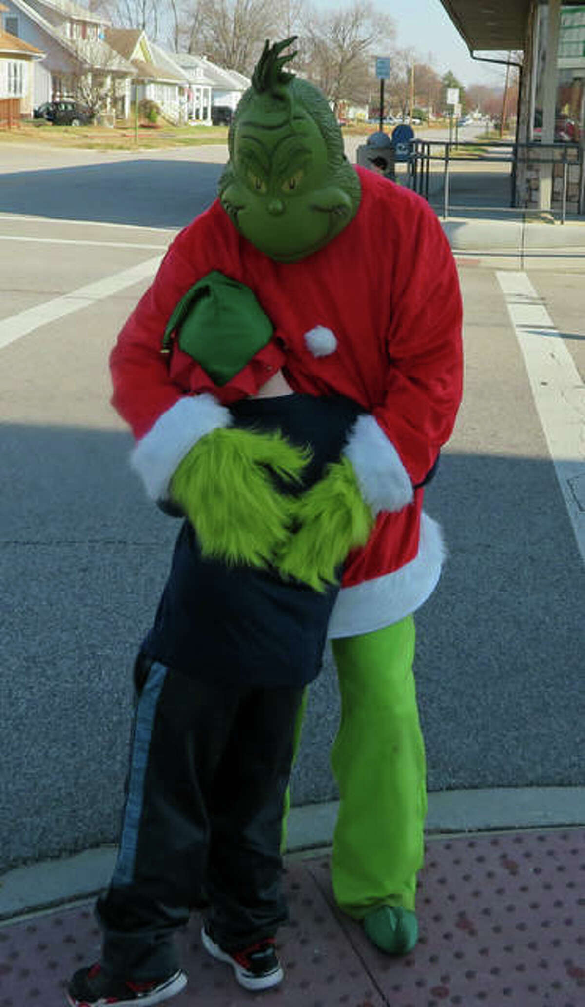 The Grinch greets a young volunteer at Saturday's Fill Santa's Semis event in Wood River.