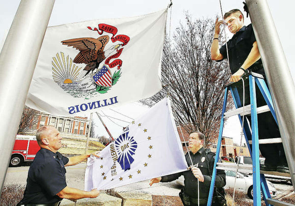 Alton Fire Chief Bernie Sebold, left, and Alton Police Deputy Chief Terry Buhs, right, unfold the new Illinois Bicentennial Flag as probationary firefighter Richard Sherman, far right, prepares to raise it Monday underneath the regular Illinois flag at Alton City Hall. The flag ceremony, like several across the area, was a brief part of a noon event to mark the kickoff a year-long celebration of the state's bicentennial, which occurs in December 2018.