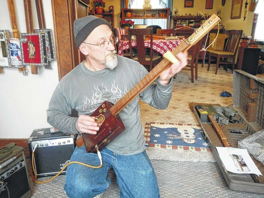 Logan Elliott strums a few chords on one of his handmade cigar box guitars. Photo: Kathleen Clark | For The Journal-Courier