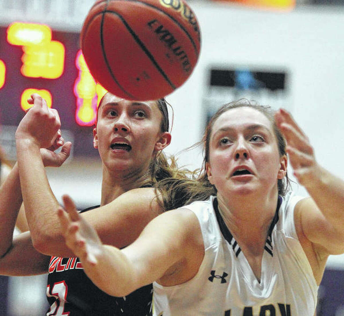 Jacksonville Routt's Bella McCartney (right) and Greenfield's Kassidy Walters go after a rebound during a WIVC girls basketball game Monday night at the Routt Dome in Jacksonville. Routt won despite 24 points from Walters.