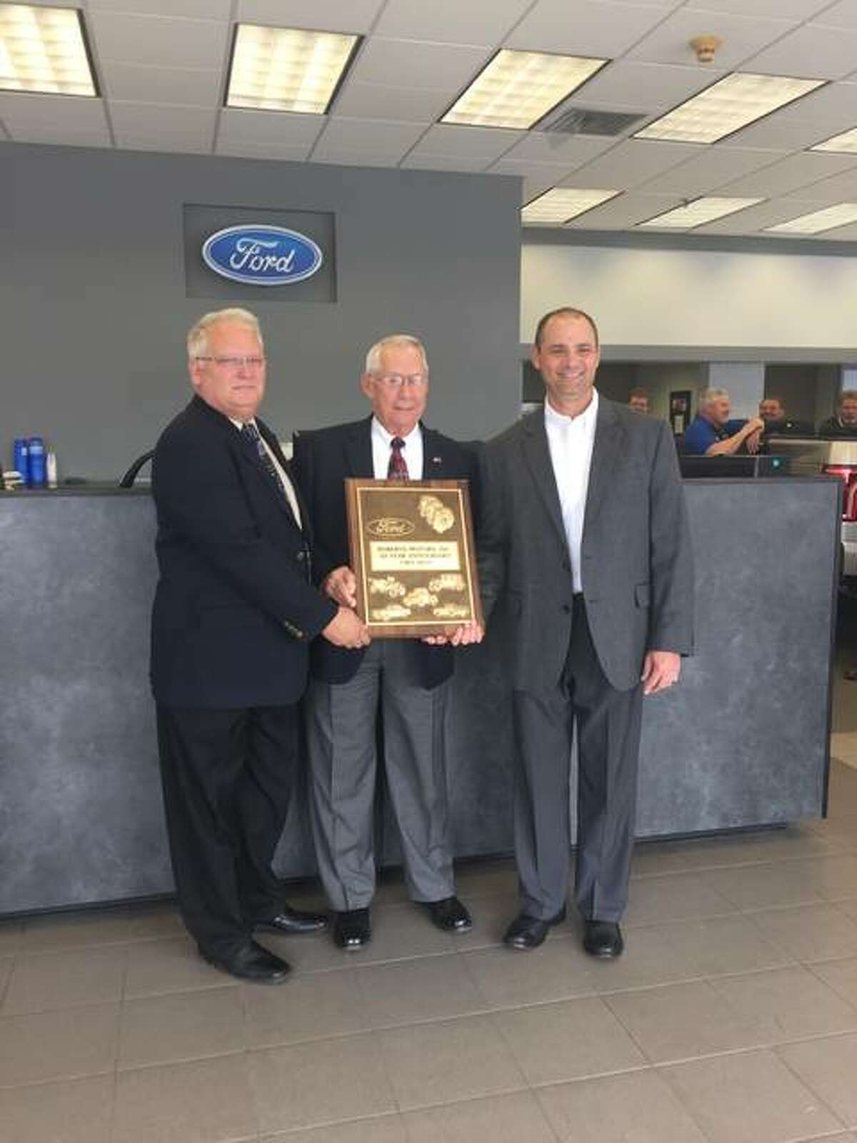 Sam Roberts, center, is one of a select group of 47 dealer nominees from across the country who will be honored at the National Automobile Dealers Association's 2018 NADA Show in Las Vegas, Nevada. Roberts Motors recently celebrated 50 years in business. The business, which specializes in Ford vehicles, received a plaque to commemorate the occasion. Also shown are, from left, regional manager Kevin Klossner and general manager John Roberts.