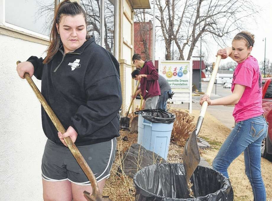 Jacksonville FFA members Allison Wheeler (left) and Annie Jackson (right) help clear rock Monday from flower beds around the Dream Center Foundation building. Dream Center members and FFA members will build a butterfly and hummingbird garden at the site. Photo: Samantha McDaniel-Ogletree   Journal-Courier