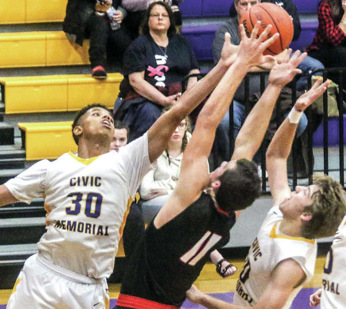 Civic Memorial's LaQuan Adams (30) battles for a rebound with Highland's Sam LaPorta (11) in Mississippi Valley Conference action Tuesday night in Bethalto. Adams scored 24 points, but Highland edged the Eagles 58-57 in overtime.