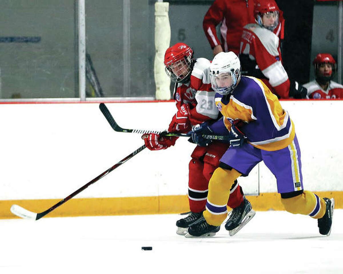 Civic Memorial's Nolan Kahl, right, and Alton's Zach Carter battle for a loose puck earlier this season at the East Alton Ice Arena. The teams faced off again Tuesday night and skated to a 2-2 tie at East Alton.