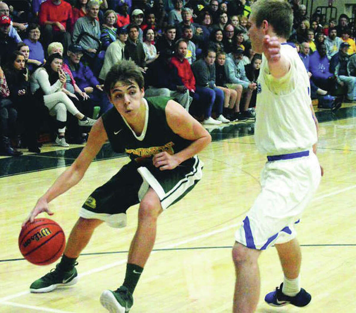 Metro-East Lutheran's Jonah Odgen (left) is cut off by Marquette Catholic's Sammy Green during the title game of the MEL Thanksgiving tourney No. 25 at Hooks Gym in Edwardsville. The teams met again Tuesday night in Alton, with Marquette again defeating MEL to keep the Explorers unbeaten at 7-0.