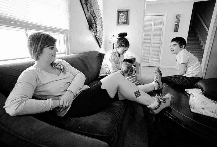 In this Wednesday, Jan. 11, former skinhead Shannon Martinez, left, talks with some of her children in their home in Athens, Ga. A member of the racist group starting in her teen years, Martinez quit decades ago and is now worried about a possible rise in extremism in the United States. AP Photo | Jay Reeves