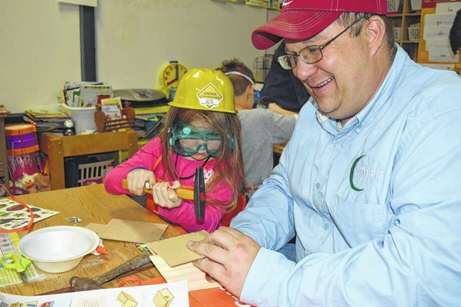 Claire Harris, the 5-year-old daughter of Jay and Mary Beth Harris of rural Jacksonville, helps her dad make a birdhouse Tuesday night at Salem Lutheran School, where she attends kindergarten. Photo: Greg Olson | Journal-Courier