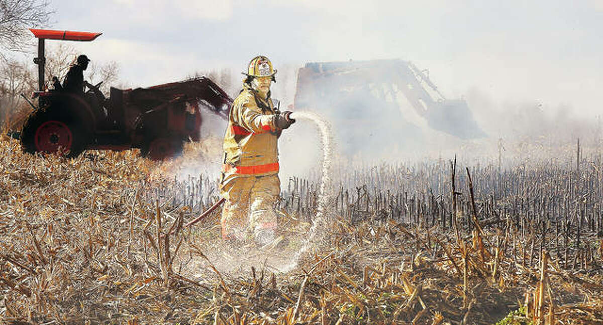 """Fosterburg Fire Chief John Holtorf wets down the edges of a cornfield stubble fire that broke out Wednesday on the north side of Storey Lane in Alton. Local farmers helped extinguish the fire with tractors (background) and form fire breaks to keep the fire, which panicked some nearby homeowners, from spreading. Alton called for assistance from Fosterburg, Godfrey and East Alton firefighters with Fosterburg and Godfrey bringing """"brush trucks"""" which can drive through fields to extinguish such fires."""