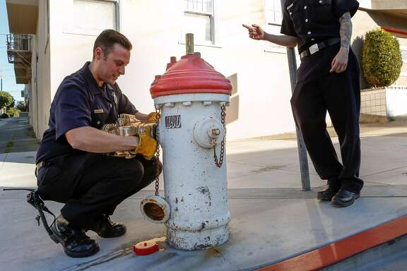 Firefighters Dillon Olivas (left) and Dani Rosenthal demonstrate how a Greeson Valve is attached to one of high-pressure system hydrants on 12th Ave and Anza St. near Fire Station 31 on Wednesday, February 7, 2017 in San Francisco, California.