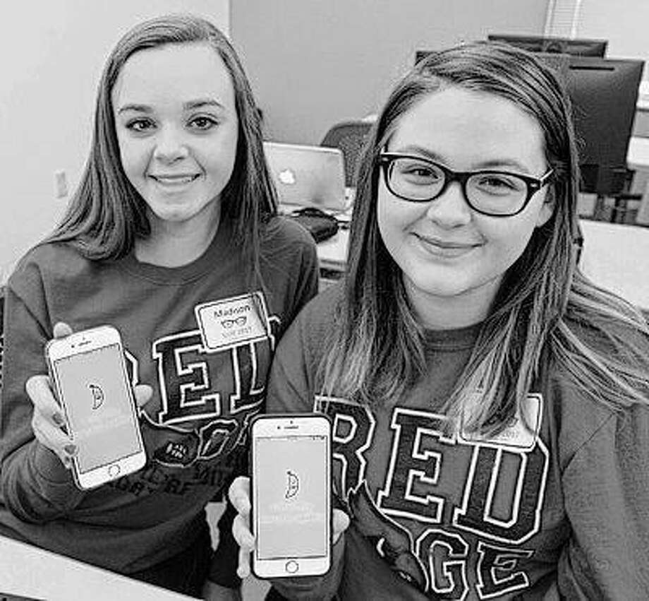 Madison Wallace and Anna Miller, sophomores at Alton High School, display the mobile app they created during SIUE's SheCode event. Photo: For The Telegraph