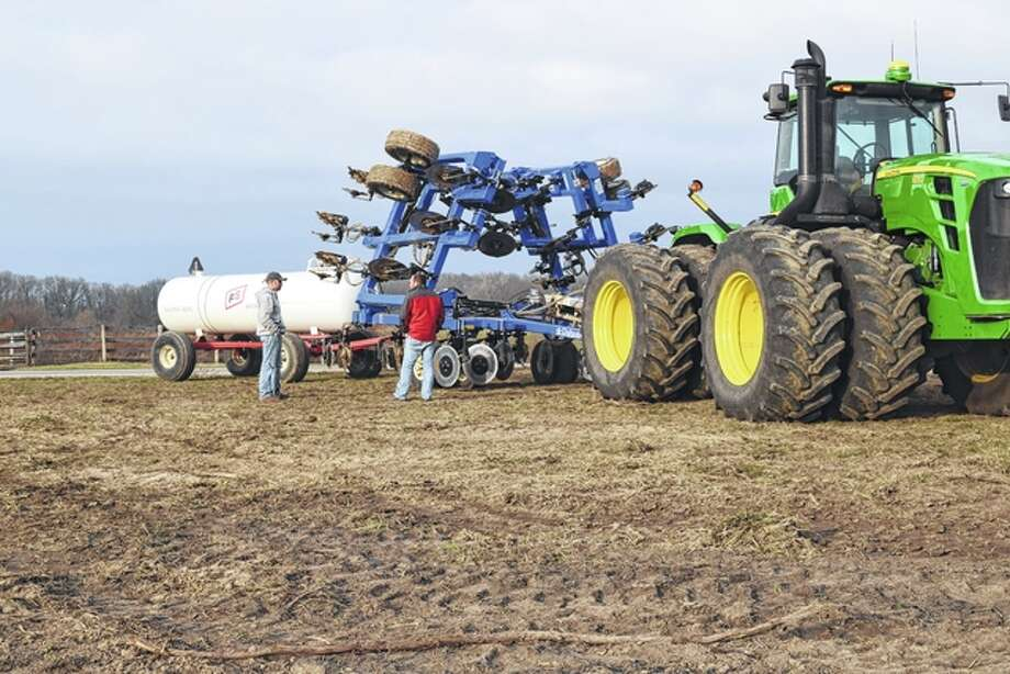 Brothers Kyle Schone (left) and Chad Schone stand near a tractor, anhydrous ammonia applicator and an anhydrous tank Thursday in a field west of Bethel. Photo: Greg Olson | Journal-Courier