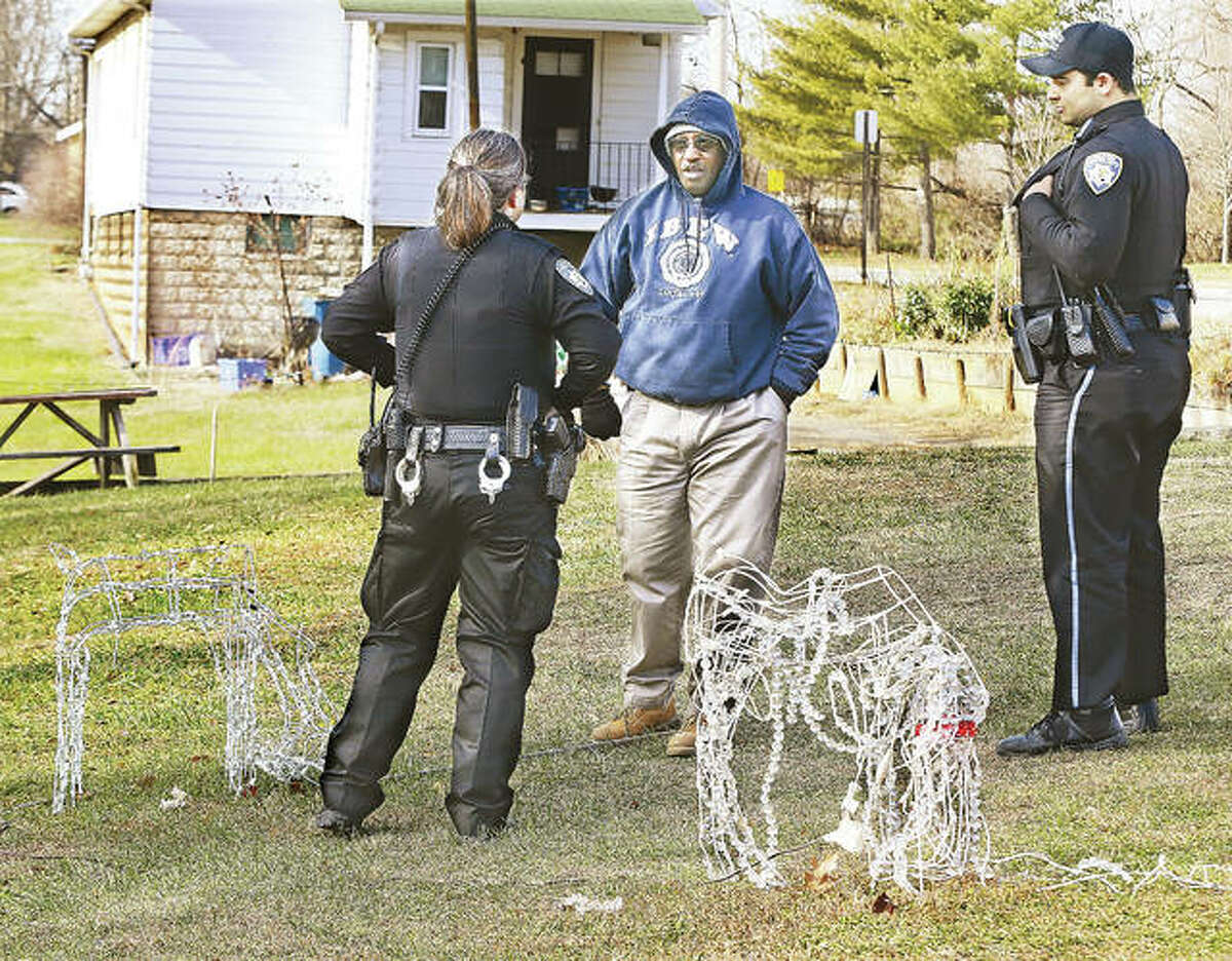 Joe Elliott, center, talks to Alton Police Thursday about vandalism to Christmas decorations in the lot at the corner of Johnson and Riley streets in Alton that included the beheading of at least two lighted reindeer, foreground.