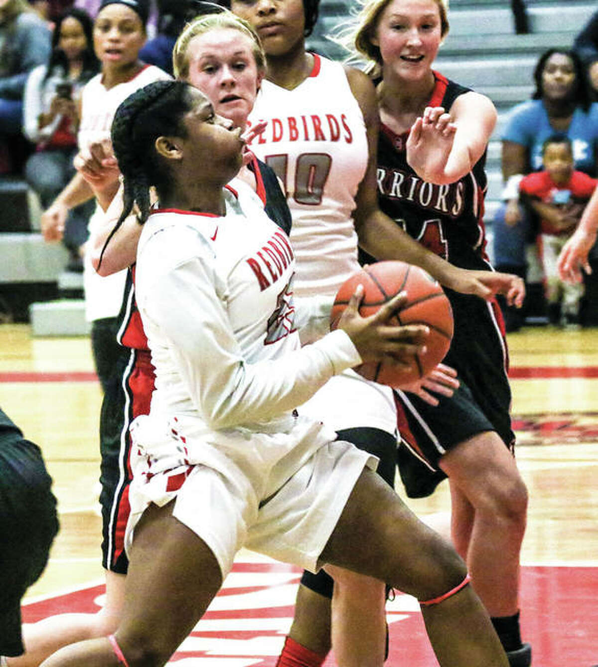 Alton's Haninah Hamilton (front) goes up for a shot during a game against Calhoun in the Alton Tip-Off Classic tournament on Nov. 15 at Alton High in Godfrey. The Redbirds were on the road Thursday night and snapped a 36-game Southwestern Conference losing streak by beating the Warriors 46-22.