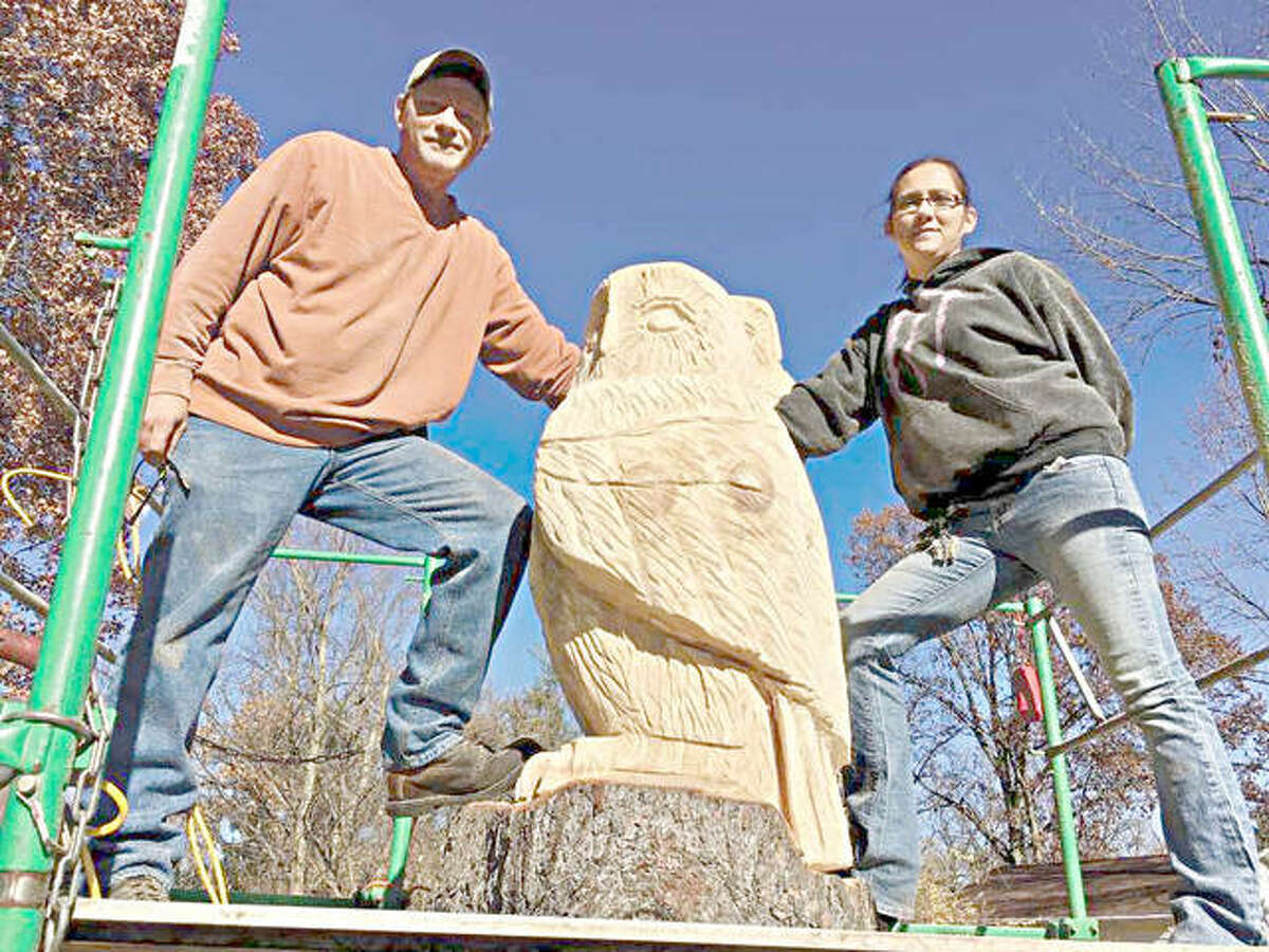 Brian Willis and Jessica Kuehnel of Chainsaw Sculptures in Granite City work on their project on Franklin Avenue.