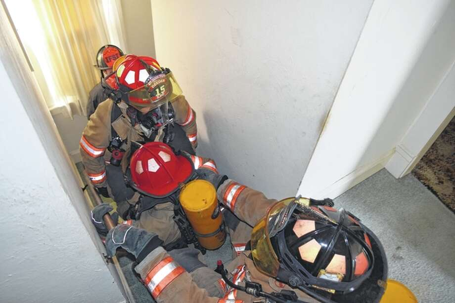 South Jacksonville firefighters move a downed firefighter up a flight of stairs Saturday during a training session.
