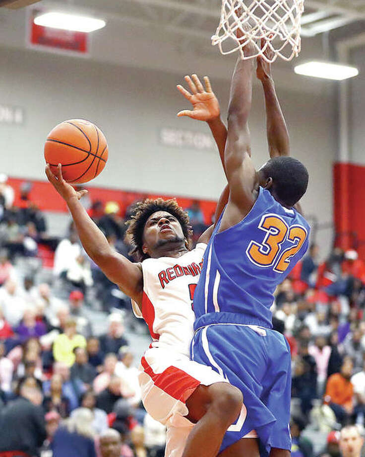 Alton's Darrell Smith, left, drives to the basket while guarded by East St. Louis' Traeveion Jones during Friday's Southwestern Conference game at Alton High School. Photo: Billy Hurst | For The Telegraph