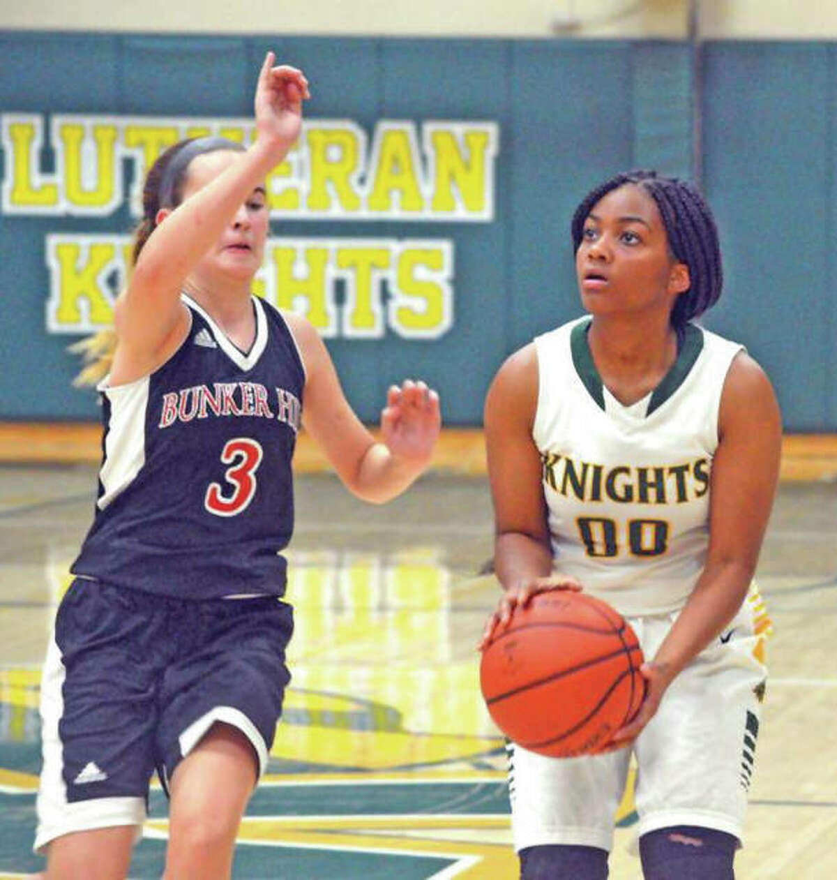Metro East Lutheran's Destiny Williams (right) looks to shoot while Bunker Hill's Brylie Chrisman defends during Friday's game Prairie State Conference girls basketball game at Hooks Gym in Edwardsville. The Minutemaids got a career-high 35 points from Mallory Schwegel in a 68-49 victory.