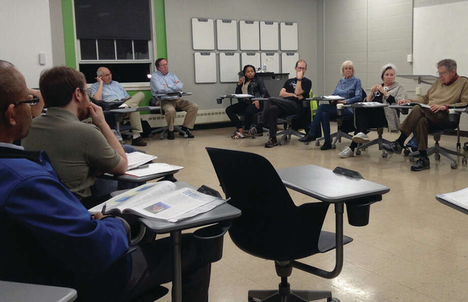 Two dozen people have been meeting weekly to discuss the state of the world. This year's sessions are facilitated by Illinois College professor Winston Wells on such subjects as U.S. involvement in world trade, emerging countries and Central America policies. Photo: Photo By Jeannie Hemphill