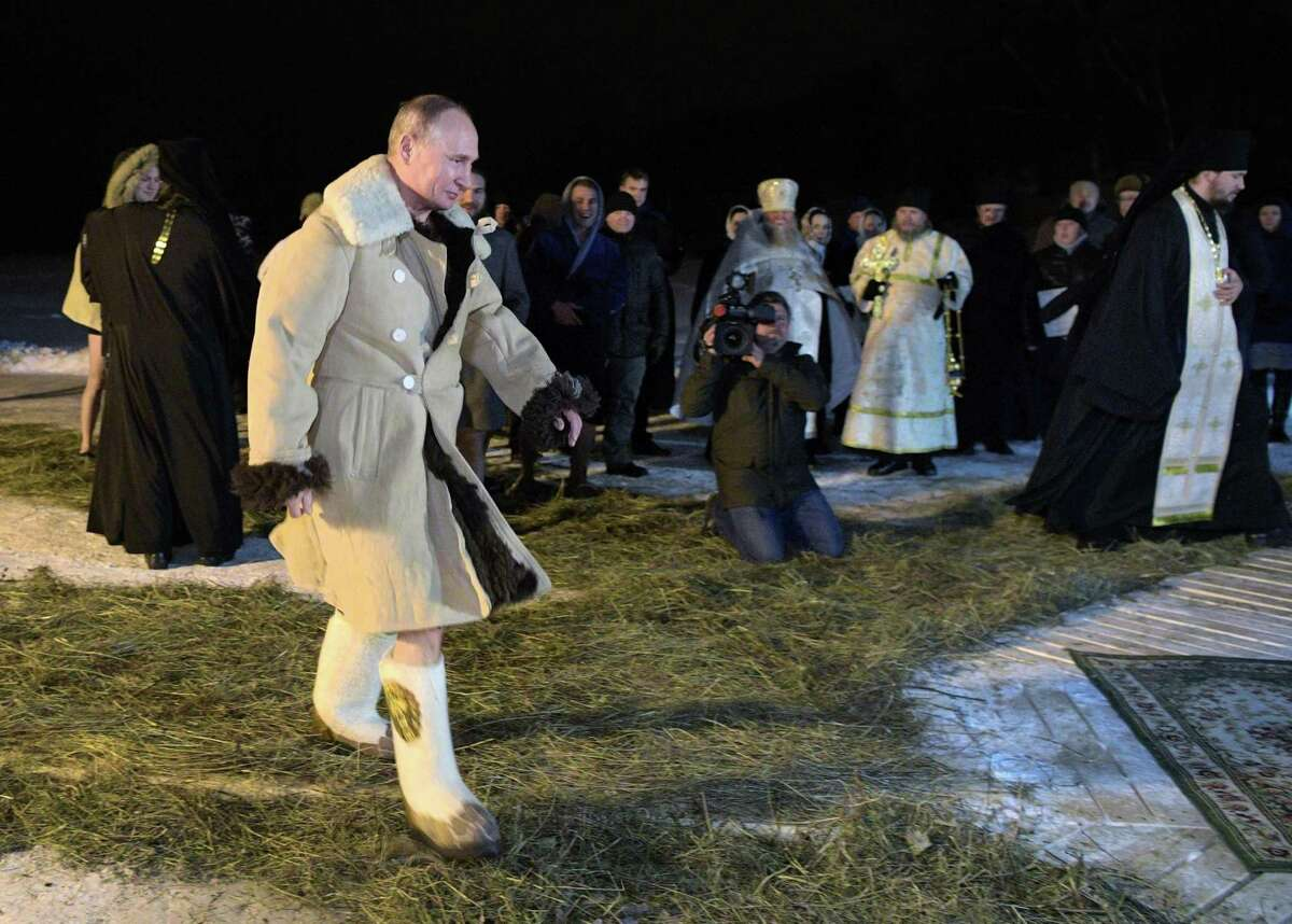 Russian President Vladimir Putin dressed in sheepskin coats walks to bath in an ice-cold water on Epiphany neat St. Nilus Stolobensky Monastery on Lake Seliger in Svetlitsa village, Russia, Friday, Jan. 19, 2018. Russia and China are big buyers of Texas sheepskin.