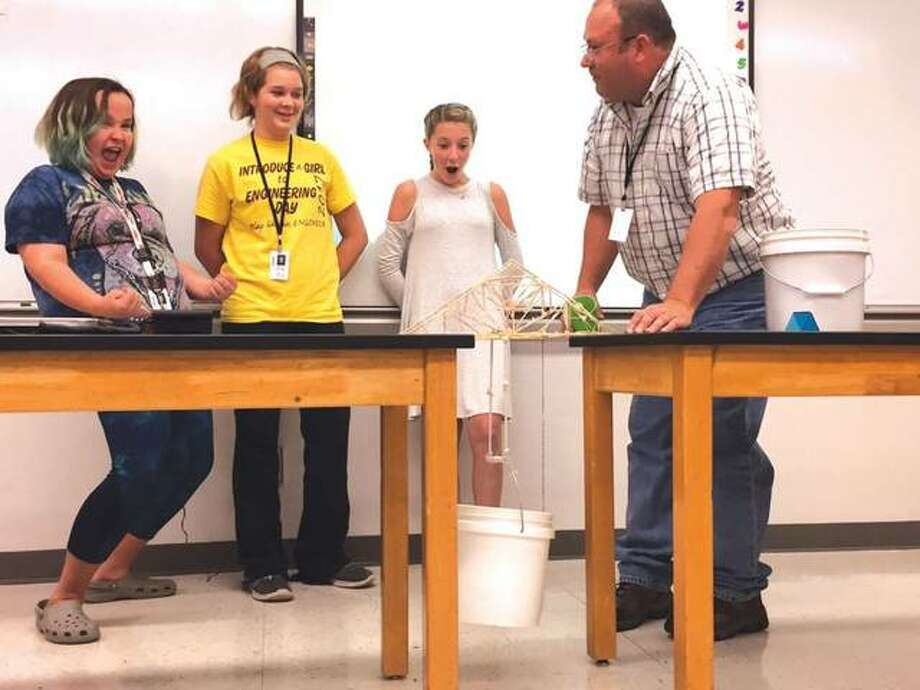 Lincoln Middle School teacher Gardner Holland watches the reaction of students Grace Ramsey, Abby Brown and Taylor Mollett as their toothpick bridge holds additional weight. Photo: Julia Biggs | For The Telegraph