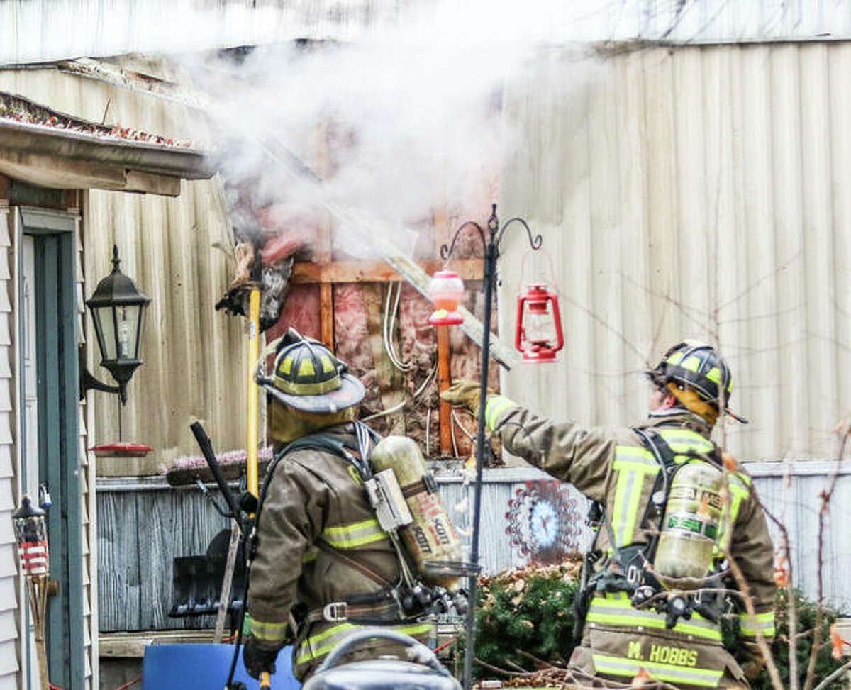 Firefighters peel paneling from the outside of a trailer that caught fire Saturday afternoon at 213 Illinois Ave. in South Roxana. The fire, which appeared to originate inside of a wall, caused extensive smoke damage to the home.