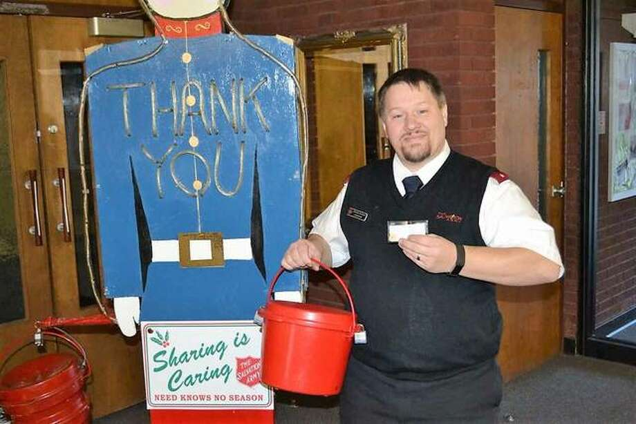 Alton Corps officer Lt. Stephen Reinier poses with one of the red kettles during the 2017 Salvation Army – Alton Corps' Red Kettle campaign. Last Monday, Reinier opened up a red kettle and found an American Gold Eagle gold coin folded inside a note. Photo: For The Telegraph