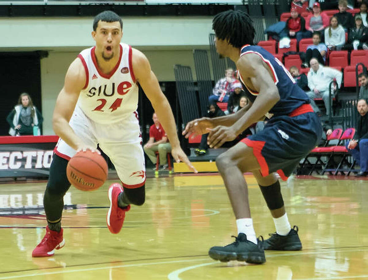 SIUE's Jalen Henry (left) drives on a South Alabama defender during the Cougars' victory Sunday afternoon at Vadalabene Center in Edwardsville. Henry, a senior from Springfield who had 26 points and 12 rebounds, converted two free throws with 3.5 seconds left to give the Cougars a 76-75 victory.