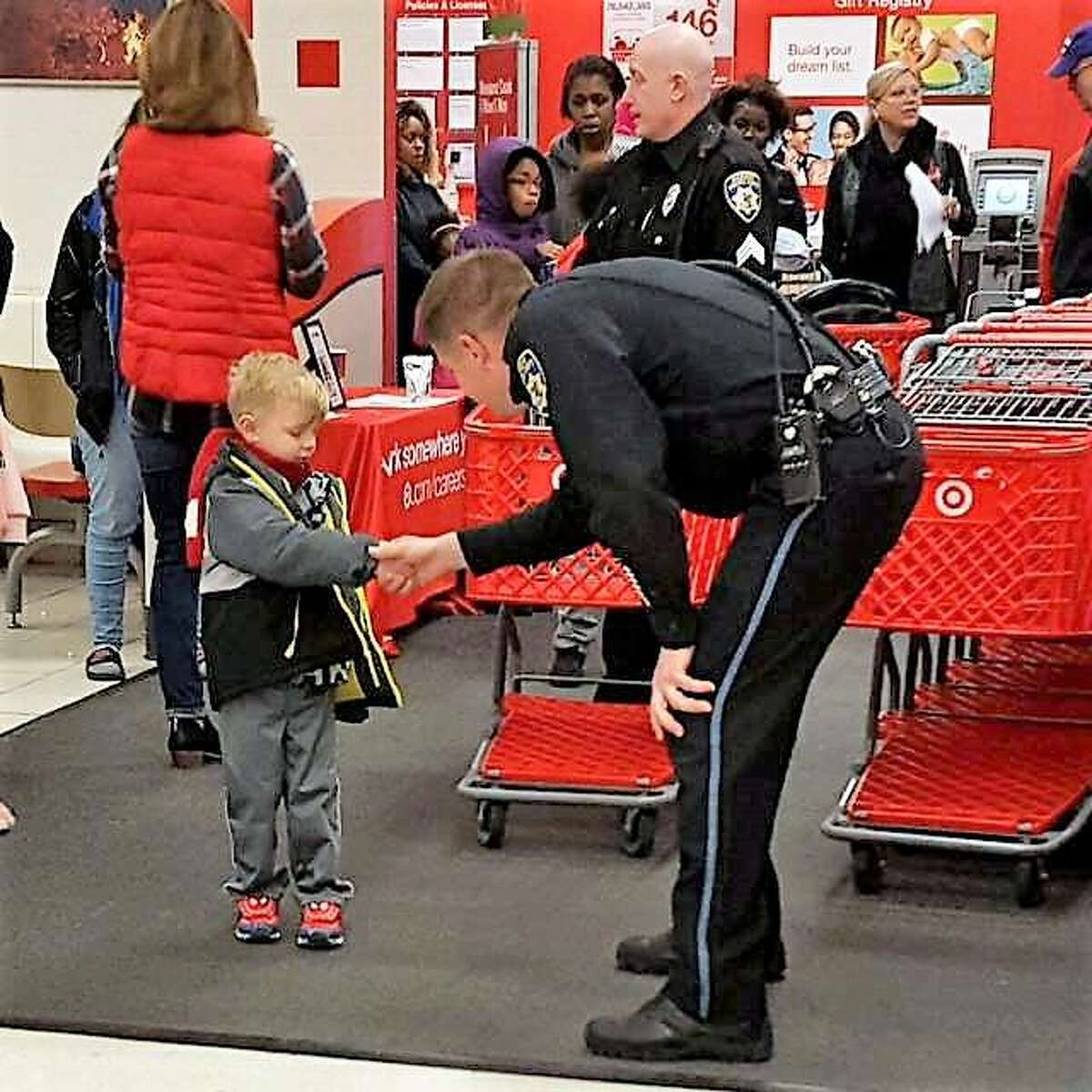 An Alton police officer greets a young student ready to shop at Target Saturday during this year's Shop with a Cop event. Members of the Police Benevolent and Protective Association Alton Unit 14 took children on a shopping spree for the annual outreach activity.