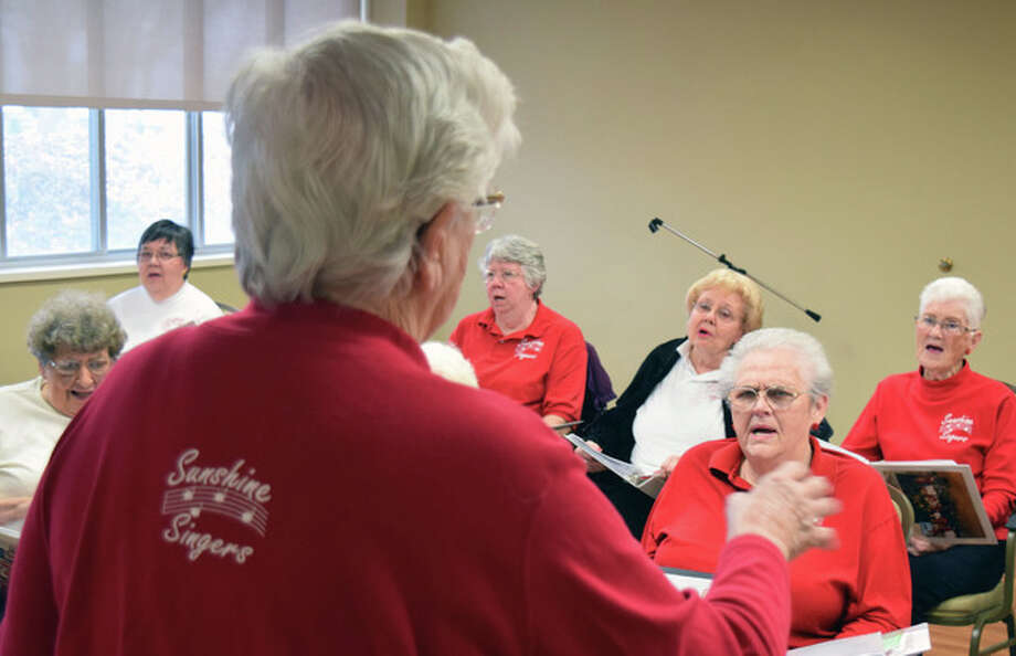 "Mary Ann Turner leads the Sunshine Singers, a Jacksonville Area Senior Center chorus, in a rendition of ""America the Beautiful"" at Heritage Health on Tuesday. The group sings frequently at the senior center and also makes visits to nursing homes."