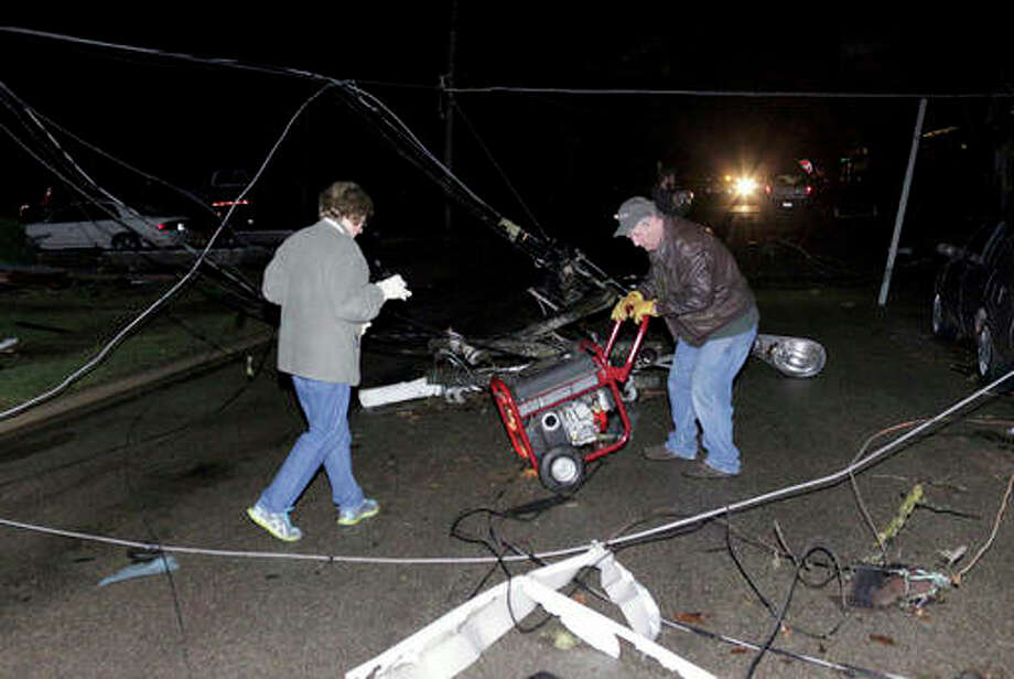 Chris Yucus | News Tribune (AP) A man and woman try to wheel a portable generator through downed wires after a storm moved through Naplate on Tuesday. Tornadoes touched down in the upper Midwest on Tuesday.