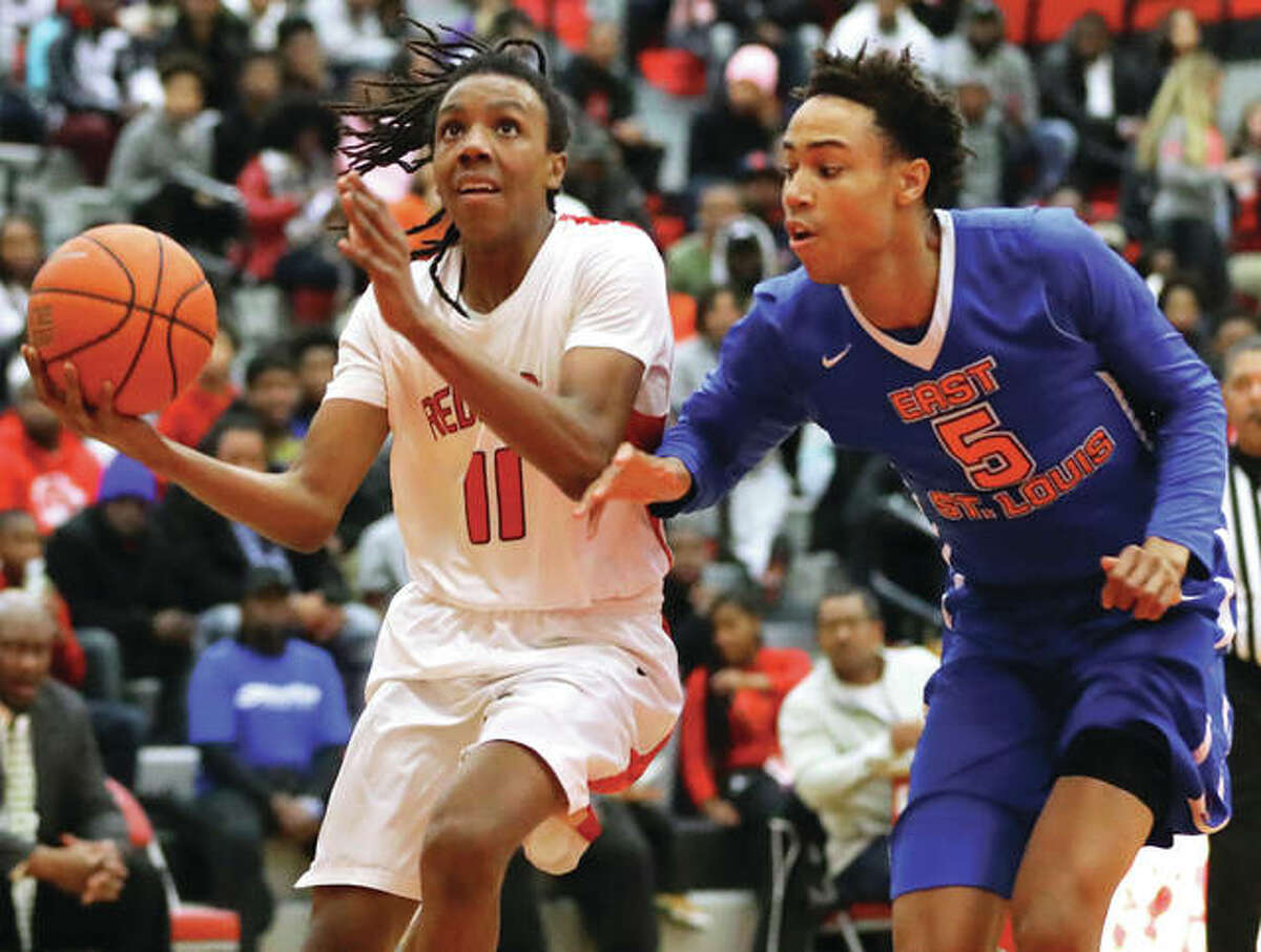 Alton's Donovan Clay (left) drives the lane past the East St. Louis' Joe Reece during Friday's Southwestern Conference game at Alton High School in Godfrey. Clay had 16 points, including 10 in the third quarter, in the Redbirds' 75-71 victory.
