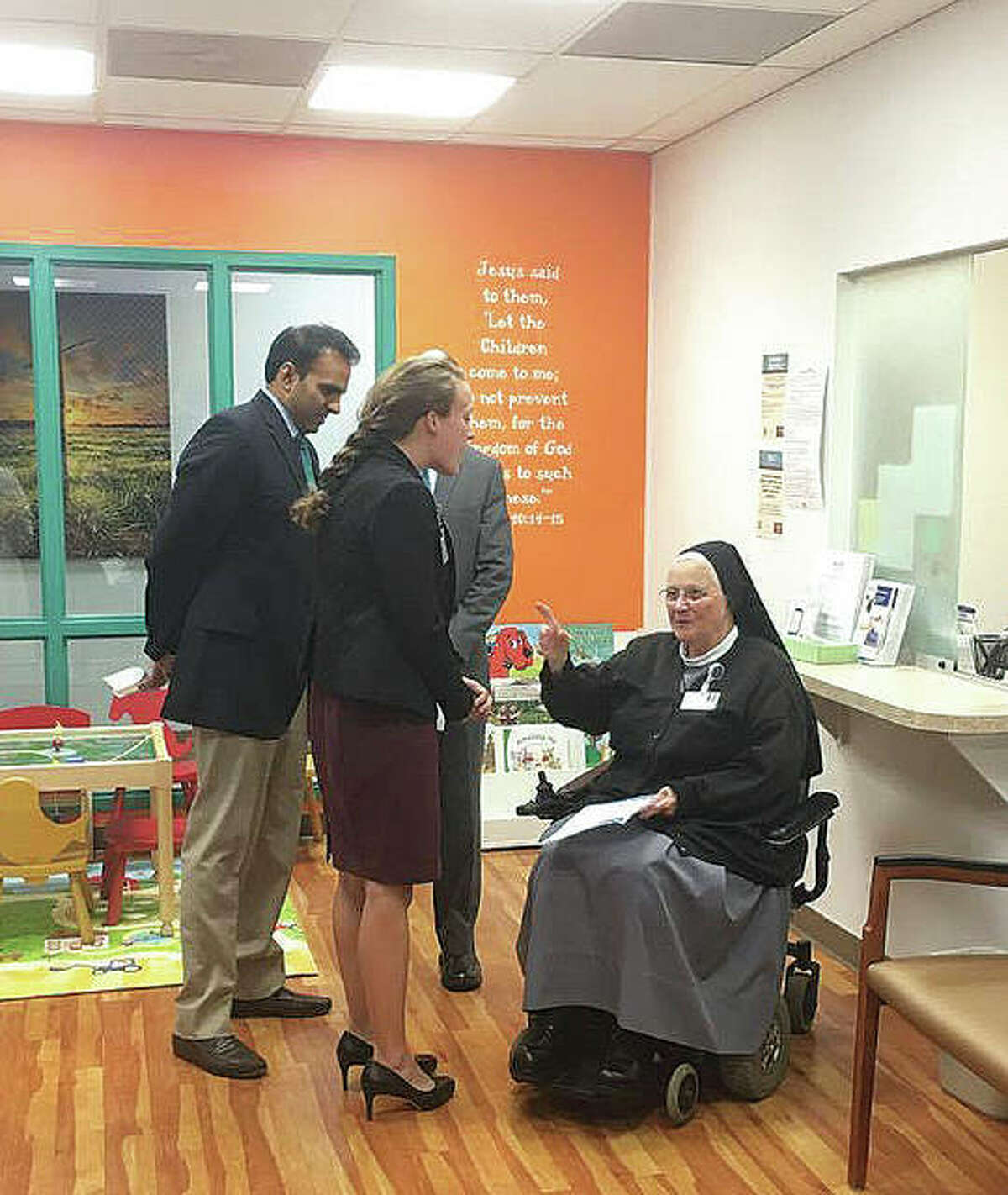 OSF Saint Anthony's Health Center's CEO and President Ajay Pathak, far left, the new pediatric office's family nurse practitioner Elizabeth Schmerold, and OSF Medical Group Operations Manager David Wells, behind Schmerold, talk with Sister M. Dominica, who sang with the Sisters of St. Francis of the Martyr St. George choir at a blessing and open house last Thursday for OSF Saint Anthony's Health Center's first pediatric office.