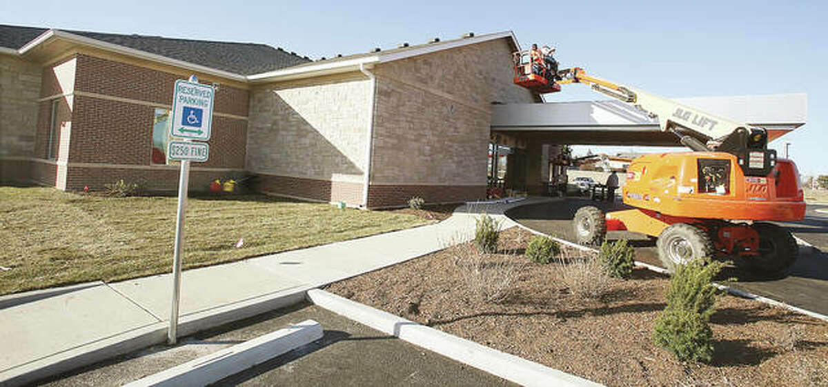 Workers put finishing touches on the exterior of the new OSF HealthCare primary and urgent care facility in Godfrey Monday.