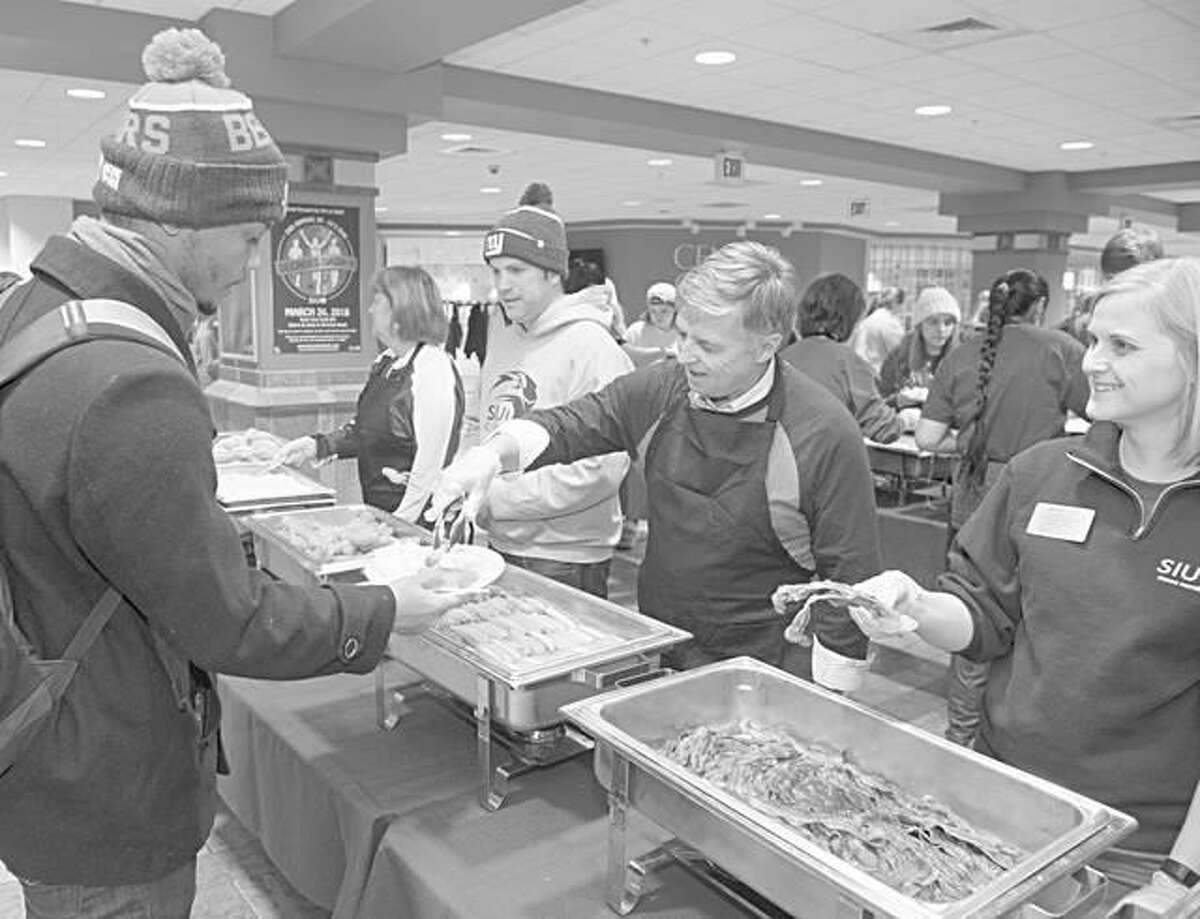 SIUE Chancellor Randy Pembrook serves junior Nicholas Haley, of Springfield, during the late night breakfast.