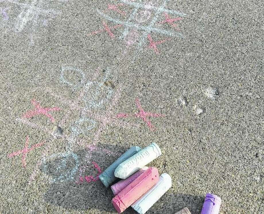A sunny day earlier this week and a clean sidewalk provided a perfect setting for a few games of tic-tac-toe. Photo: Joy Harris | Reader Photo