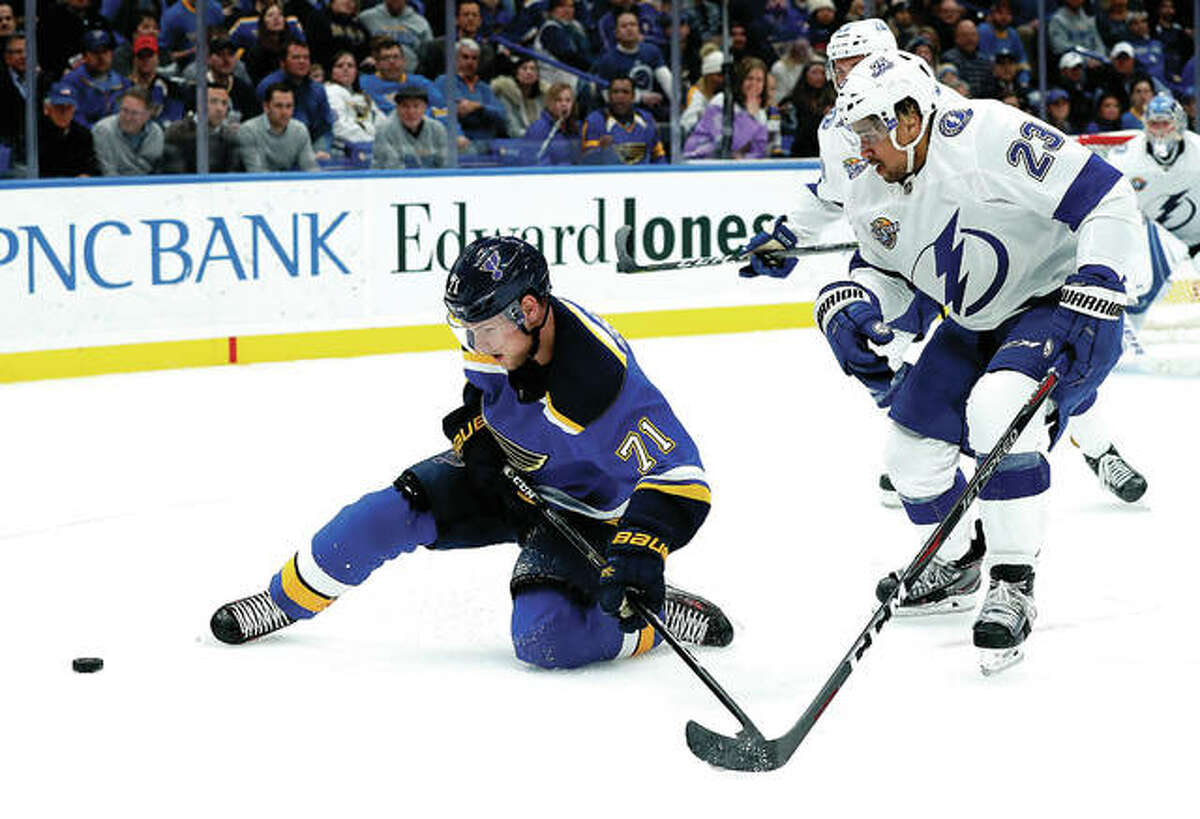 The Blues' Vladimir Sobotka, left, falls to a knee as he chases a loose puck with Tampa Bay Lightning's J.T. Brown, Tuesday night in St. Louis.
