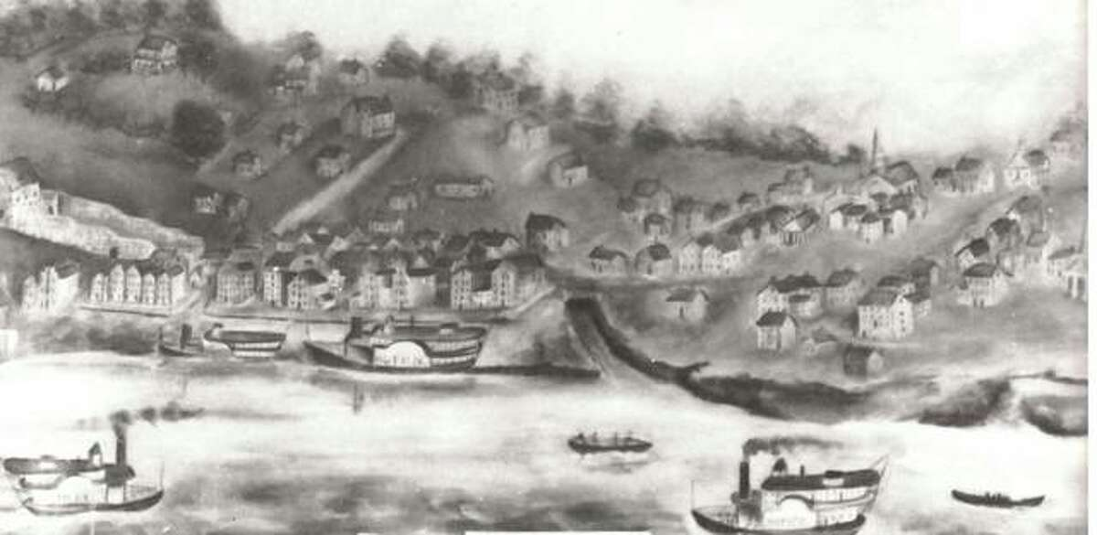 This primitive scene of Alton in 1836 was painted by W.H. Temple and for many years was the property of Mrs. George A. Savage. At the extreme left is a distillery. Next is the building where Lovejoy was slain. The steepled building on the extreme right is the First Baptist Church. The boat landing and Piasa Creek are clearly seen in the center of the painting. The penitentiary is shown and the artist has attempted to create the effect of the steep hills of Alton with the roads leading down to the Mississippi.