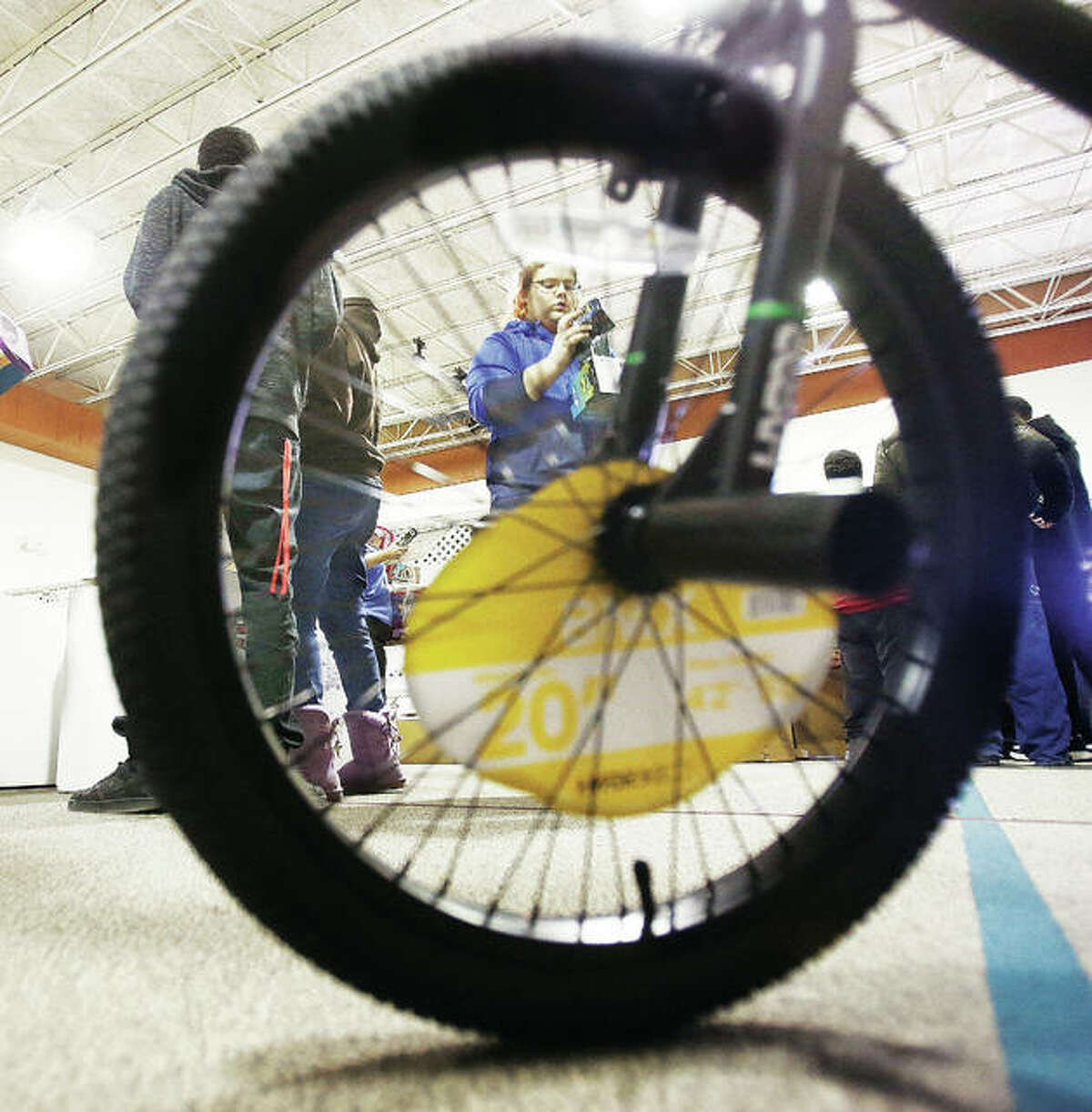 A volunteer from Alton High School, framed through the wheel of a new bicycle, helps sort Community Christmas toys last week at Main Street United Methodist Church in Alton.