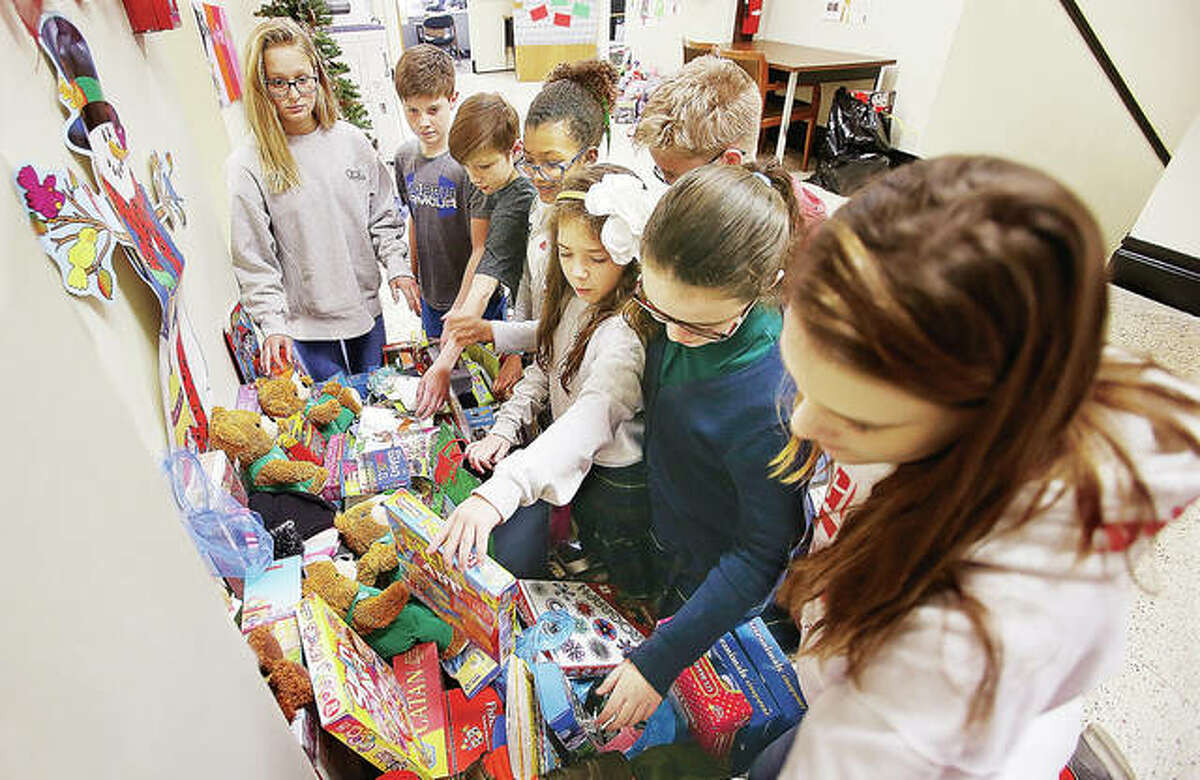 Student Council members from the fourth through eighth grades look at the toys collected by the entire school Wednesday at Ss. Peter and Paul School, 801 State St. in Alton. The toys were collected for Caritas Family Solutions foster care program.