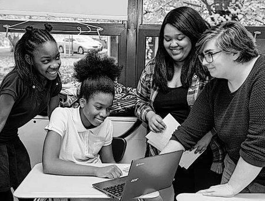 Middle school students from Madison, Monique Wright and Karmen Jackson, work with SIUE students Shervonti Norman and Gabrielle Borders during Digital Humanities Club. Photo: For The Telegraph