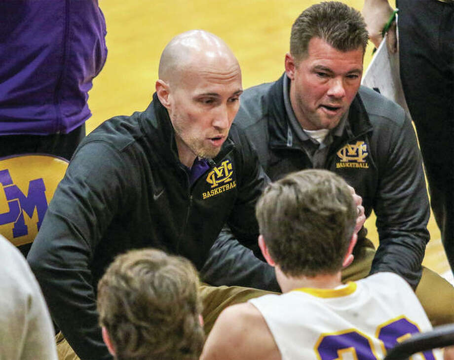 CM coach Ross Laux addresses his team while assistant coach Chris Zupas (right) listens in during a timeout in a Dec. 5 game against Highland in Bethalto. CM has lost three of four games after a 4-0 start. Photo: Nathan Woodside/ For The Telegraph