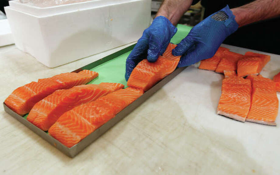 "Canadian certified organic farm-raised King Salmon filets are placed on a tray in 2015 in a store in Fairfax, Virginia. Overeating or under-eating 10 foods and nutrients contributes to nearly half of U.S. deaths from heart disease, strokes and diabetes, a study released Tuesday suggests. ""Good"" foods that were under-eaten include nuts and seeds; seafood rich in omega-3 fats, including salmon and sardines; fruits and vegetables; and whole grains. Photo: Alex Brandon 