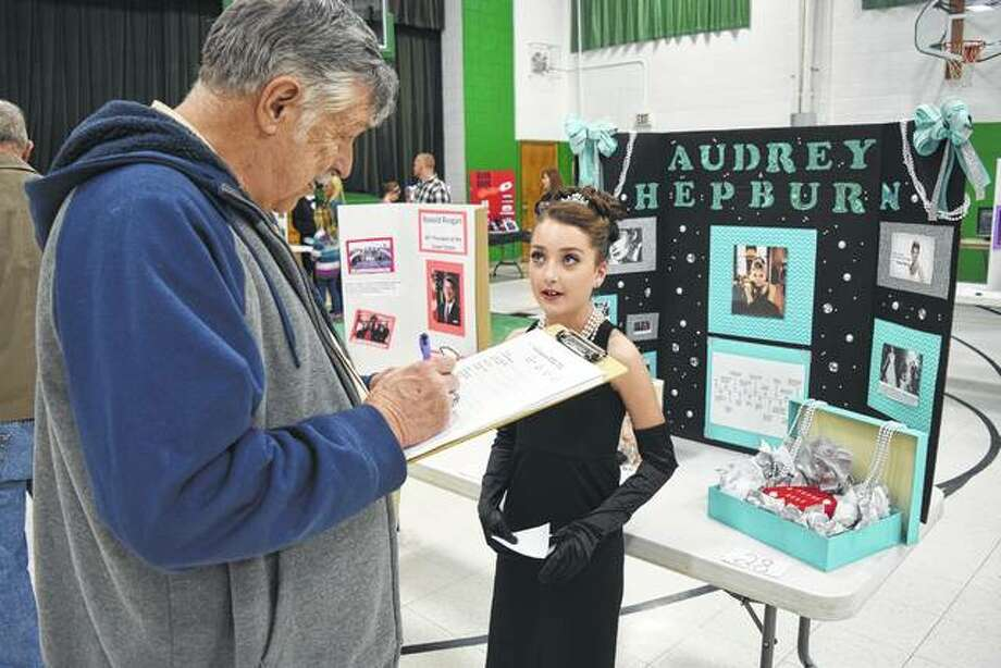 Judge Rich Ahrens of Arenzville listens to a presentation by Salem Lutheran School sixth-grader Ellieana Walden on actress Audrey Hepburn on Tuesday during the school's Living Wax Museum project in the school gym. Thirty-one Salem students in grades 5 through 8 wrote research papers and speeches and made posters about prominent people. At the Living Wax Museum, the students made presentations on those people while dressed in costume. Each project was judged and awards were presented. Ellieana is the daughter of Robin and Randy Walden of Jacksonville. Photo: Greg Olson | Journal-Courier