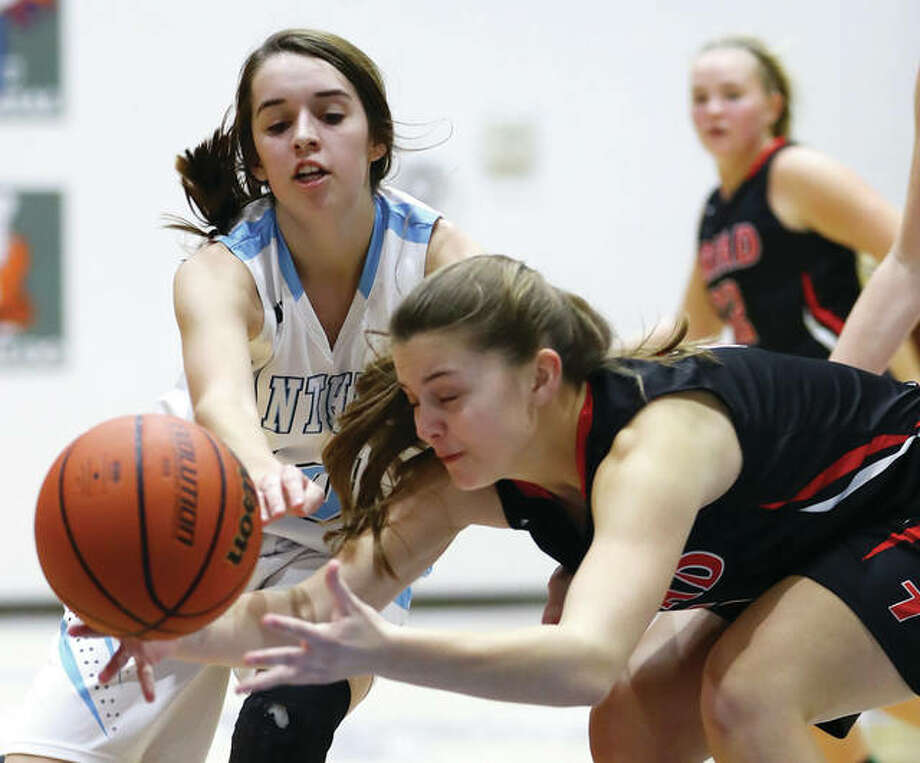 Jersey's Abby Manns (left) and Triad's Riley Fandrey (5) battle for a loose ball along the baseline during Thursday's Mississippi Valley Conference girls basketball game at Havens Gym in Jerseyville. Photo: Billy Hurst / For The Telegraph