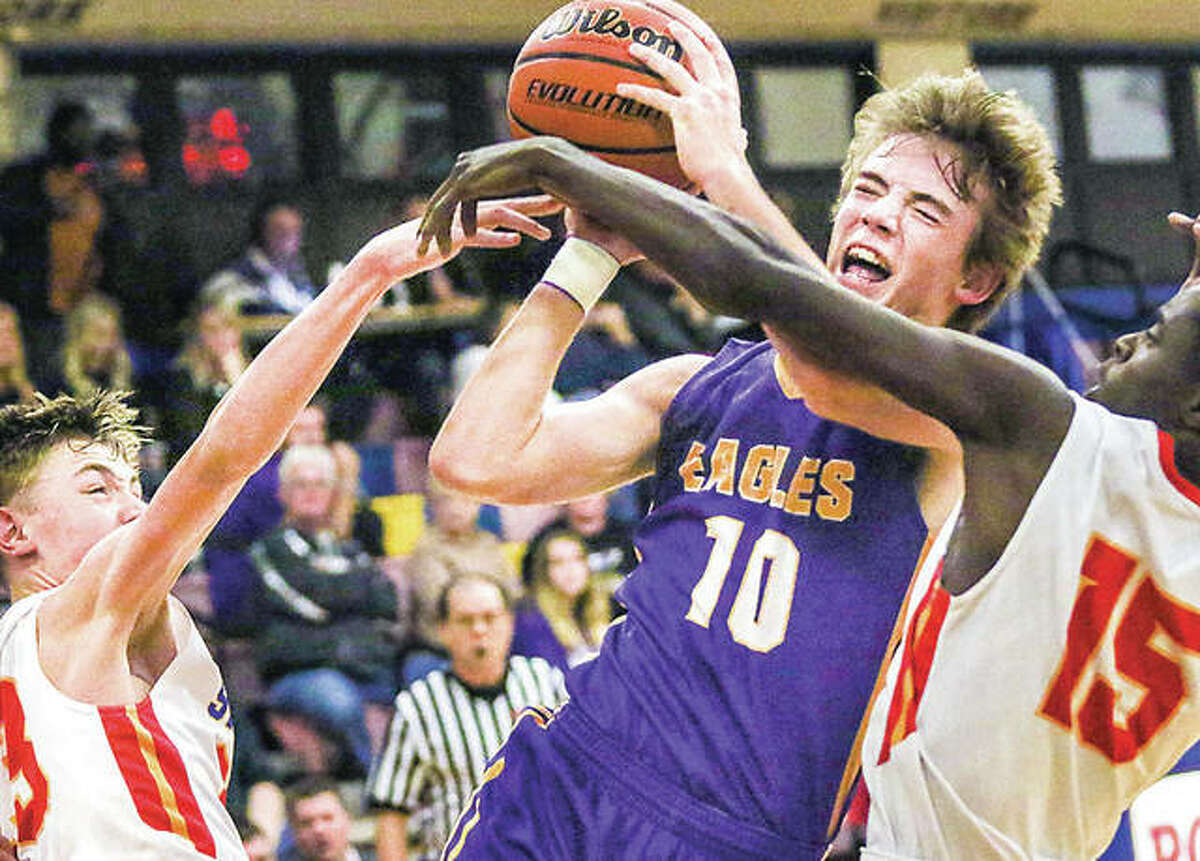 Civic Memorial's Bryce Zupan (10) draws a foul Friday night while driving to the basket against Roxana defenders Gavin Huffman, left, and Parris White.