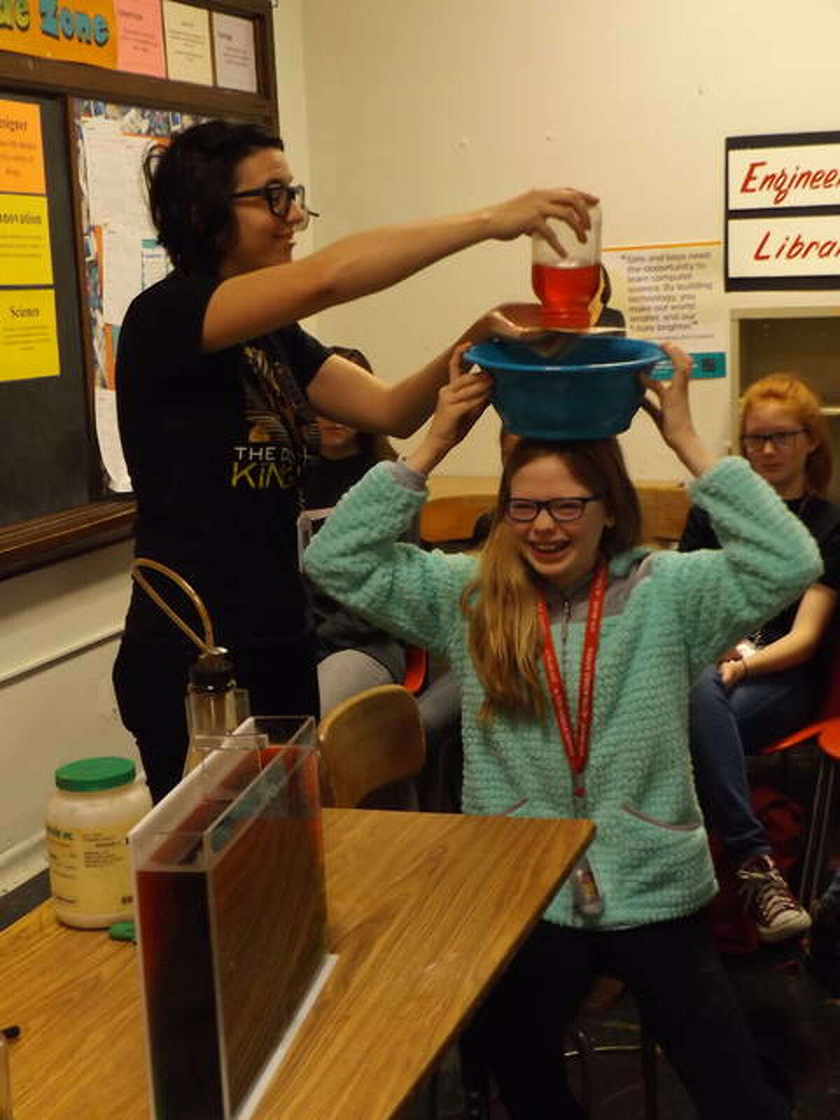 Cassandra Schneider, left, of the St. Louis Science Center's Public Programs Department, demonstrates that the surface tension of water against a screen will prevent liquid from spilling out of a jar. A student volunteer, meanwhile, hopes not to get drenched in the process.