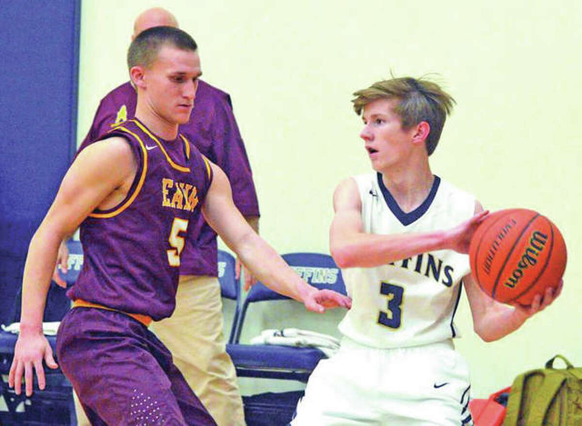 Father McGivney's Kellen Weir (right) looks to make a pass while defended by EA-WR's Justin Englar during Friday's nonconference boys basketball game in Glen Carbon. The Oilers won 49-36.