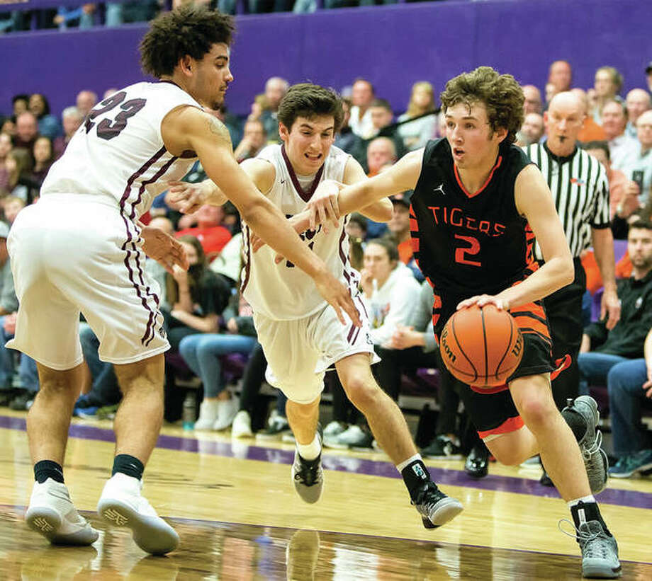 Edwardsville's Jack Marinko (right), shown driving to the basket past Belleville West's Elijah Powell (left) and Jack Lanxon during last season's Class 4A sectional semifinal at Fletcher Gym in Collinsville, is averaging 27.7 points per game in the Tigers 6-1 start. Photo: Scott Kane / Telegraph File Photo